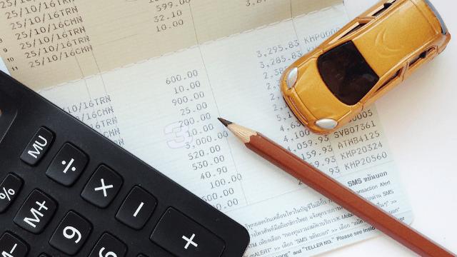 Taschenrechner liegt neben einem Bleistift und einem Spielauto auf einer Zahlenkalkulation