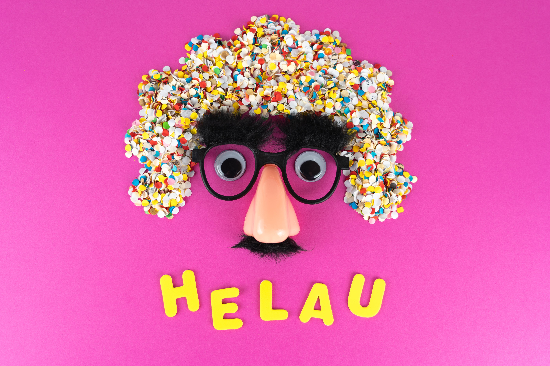 Pinker Hintergrund mit einem Gesicht gebastelt aus konfetti und einer Nasenmaske