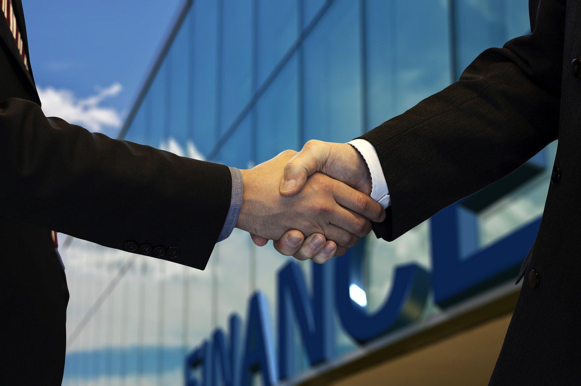 Zwei Hände mit Anzugärmel geben sich einen Begrüßungs Handschlag