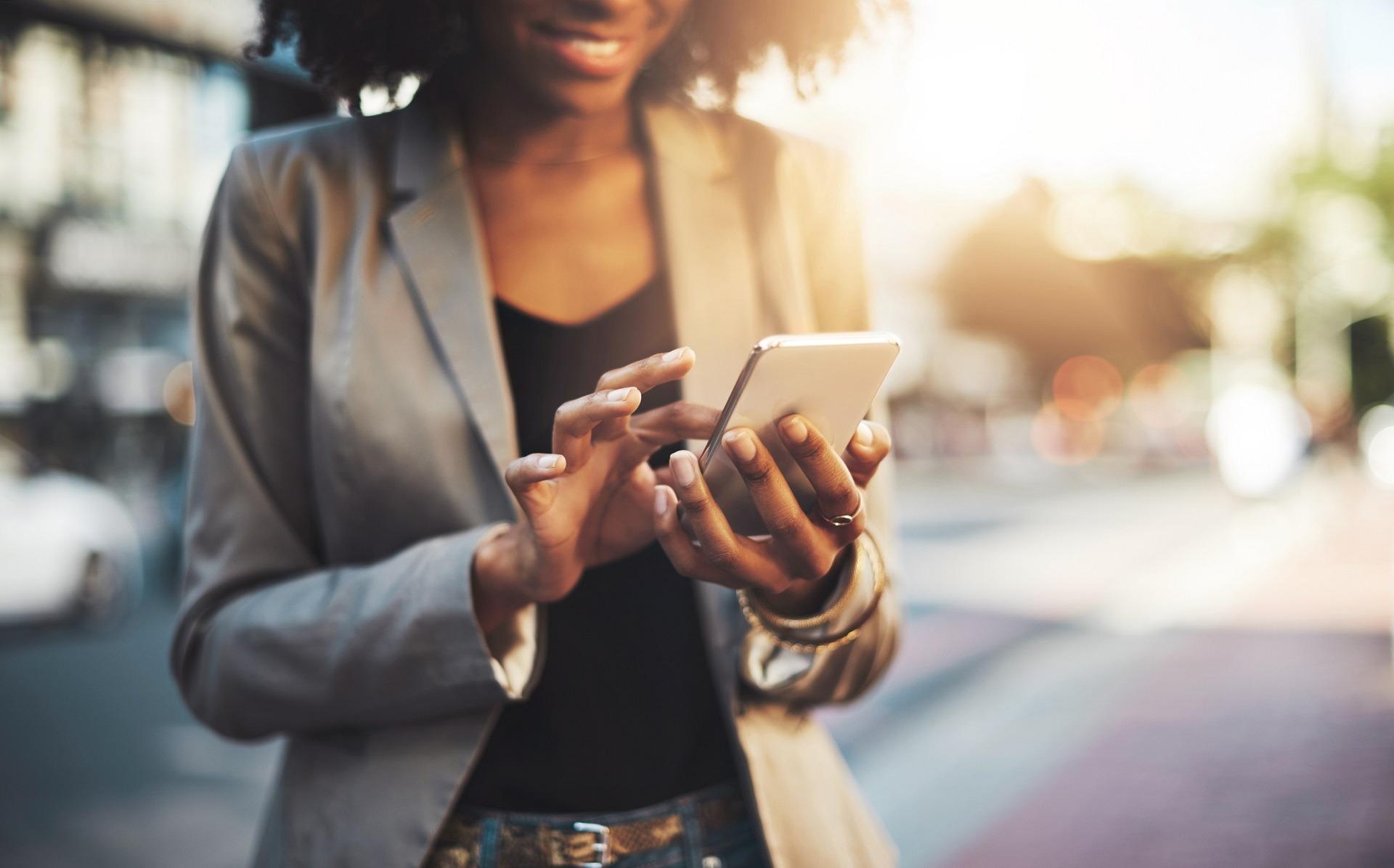 Junge Businessfrau tippt lächelnd auf ihrem Handy.