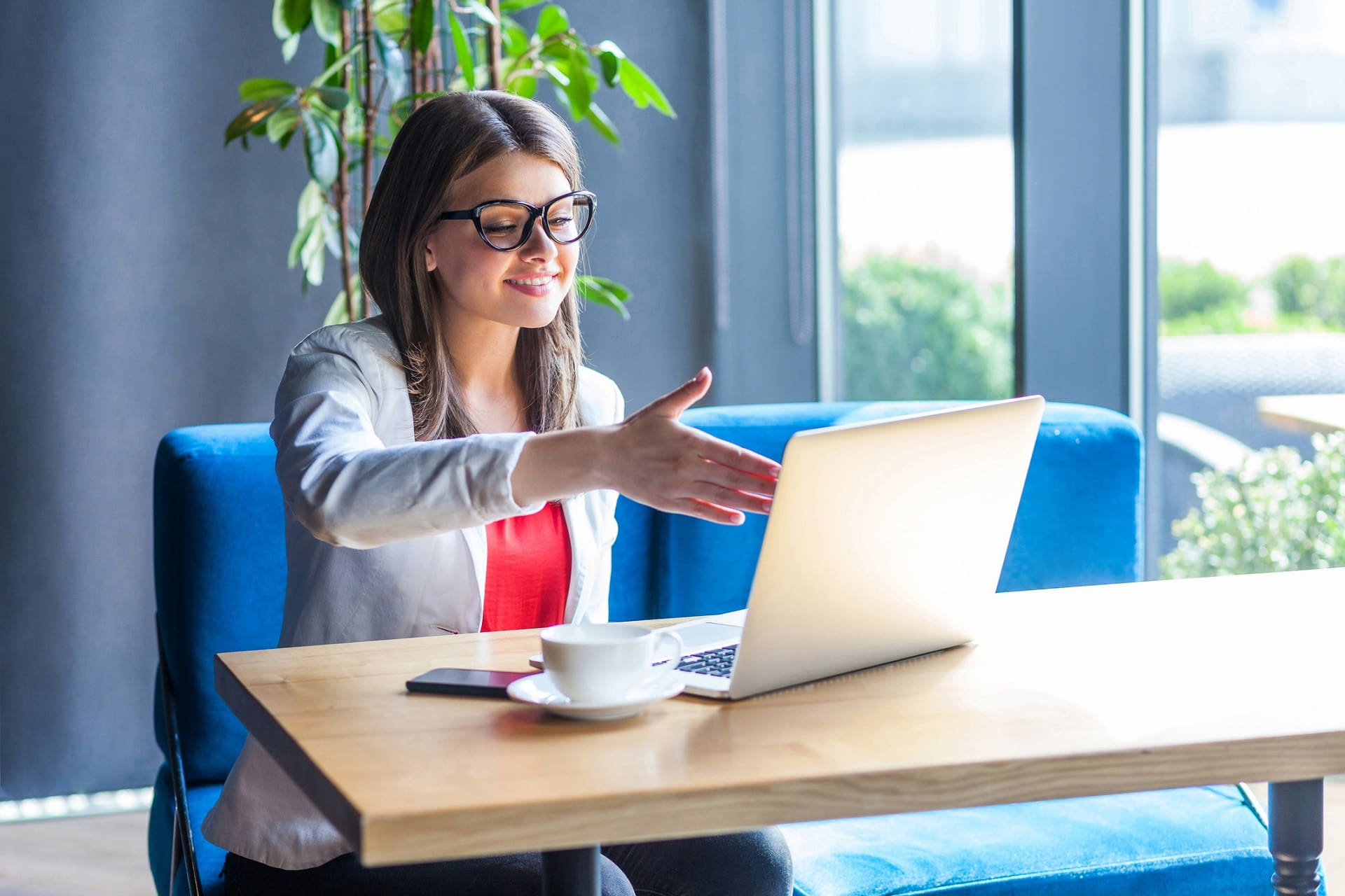Junge Businessfrau zeigt lächelnd auf einen Laptopbildschirm.